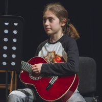 A young student on stage playing acoustic guitar reading music on a stand